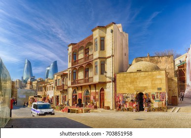 Baku, Azerbaijan - February 24, 2017: traditional street in Baku's old town with colorful historic buildings with the flame towers skyscrapers in the background