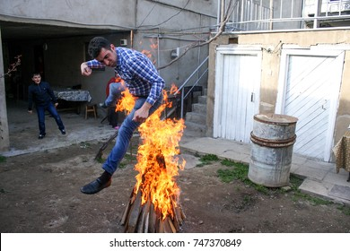 BAKU, AZERBAIJAN - MARCH 2014 - An Azerbaijani man jumps over a Novruz holiday fire, a ritual that signifies leaving the troubles of the old year and entering the new one.