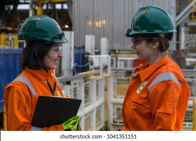 Baku, Azerbaijan - March 8 2018: Female Geologist and Engineer working on offshore oil field in Caspian Sea, discussing successful results of ongoing operation