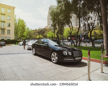 Baku, Azerbaijan - May 2, 2019: Luxury Bentley black car parked in front of Hyatt hotel in central Baku with tall trees and woman silhouette walkin in background