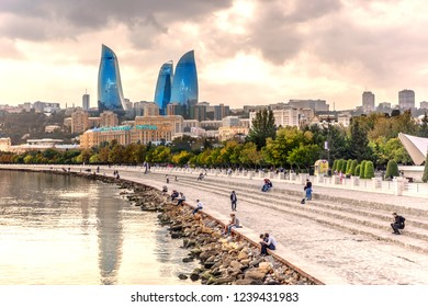 Baku, Azerbaijan - Oct 12th 2018 - Local and tourists walking in front of the Caspio sea in a late afternoon light with the Flames Towers in the background in Baku