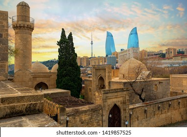 Baku city, Azerbaijan, view of the historical mosques and the walls of Shirvanshahs palace in the Old town and modern glass Flame Towers skyscrapers in dramatic sunset light