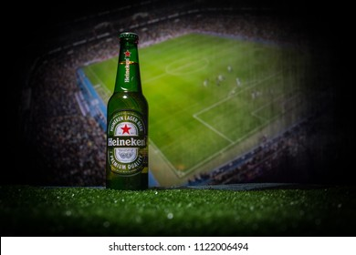BAKU,AZERBAIJAN - JUNE 21, 2018 : Creative concept. Heineken Lager Beer in bottle with Official Russia 2018 World Cup football ball The Adidas Telstar 18 on dark toned foggy background.
