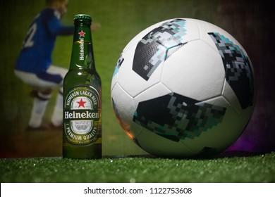 BAKU,AZERBAIJAN - JUNE 21, 2018 : Creative concept. Heineken Lager Beer in bottle with Official Russia 2018 World Cup football ball The Adidas Telstar 18 on dark toned foggy background.