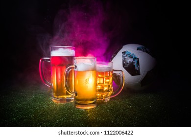 BAKU,AZERBAIJAN - JUNE 23, 2018 : Creative concept. Official Russia 2018 World Cup football ball The Adidas Telstar 18 and Beer glasses on green grass at dark toned foggy background. Selective focus