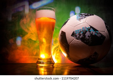 BAKU,AZERBAIJAN - JUNE 23, 2018 : Official Russia 2018 World Cup football ball The Adidas Telstar 18 and single beer glass on table at dark toned foggy background with blurred view of playing game