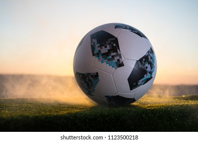 BAKU,AZERBAIJAN - JUNE 24, 2018 : Creative concept. Official Russia 2018 World Cup football ball The Adidas Telstar 18 on green grass. Sunny background. Selective focus
