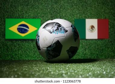 BAKU,AZERBAIJAN - JUNE 29, 2018 : Creative concept. Official Russia 2018 World Cup football ball The Adidas Telstar 18 on green grass. Brazil and Mexico. Selective focus