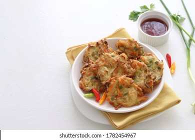 Bala-bala / Bakwan or vegetable fritter, traditional Indonesian snack, made from carrot, cabbage and bean sprouts and mix with flour and deep fried, served with chili pepper and chili sauce,copy space