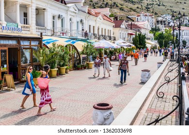 Balaklava, Sevastopol, Crimea - September 13, 2018: People stroll along the Nazukin embankment. Sunny day. Black sea