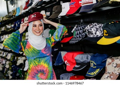 BALAKONG, SELANGOR - JULY 31, 2018. A young Muslim woman posing as she wearing used hat at the second-hand store in Balakong, Malaysia.