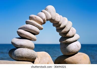 Balance arc of the white pebbles on the sea coast
