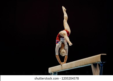 balance beam handstand female gymnast on black background
