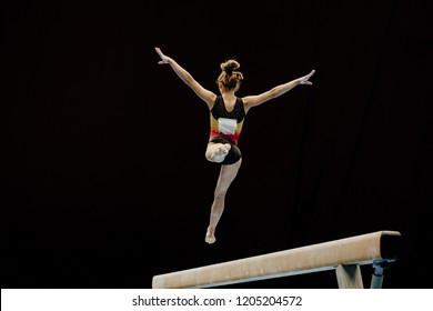 balance beam split jump female gymnast on black background