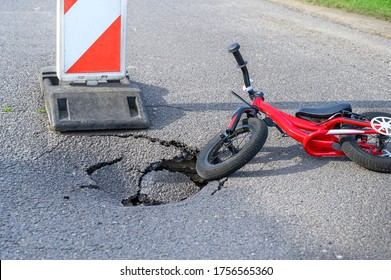 Balance bike (push bike) next to pothole on asphalt street with detour alert traffic sign