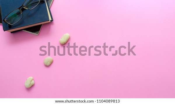 Balance concept between of Zen and work present by setting a natural zen rock stone stack, Surrounded with notebook and glasses, top view on pink background