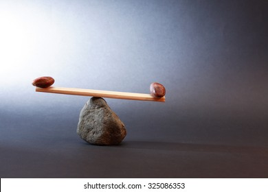 Balance concept. Seesaw made from stones and wooden plank