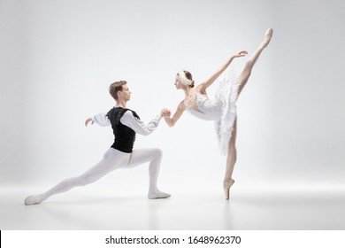 Balance. Graceful classic ballet dancers dancing isolated on white studio background. Couple in tender clothes like a white swan characters. The grace, artist, movement, action and motion concept.
