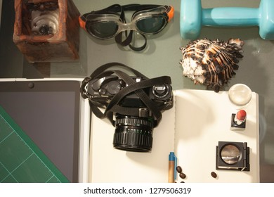 Balance and lifestyle between profession and leisure represented by camera, thread count, makeup, nail seal, cutting blade, cutting board, perfume and lipstick, weights, swimming goggles.