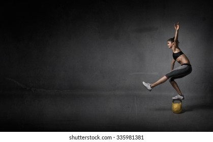 balance on a kettlebell, dark background