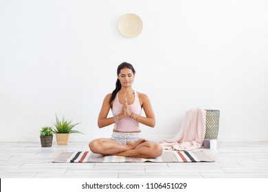 Balance and pacification. Charming dark-complexioned brunette sits in a lotus position with hands crossed in front of her on the rug in a cozy home atmosphere