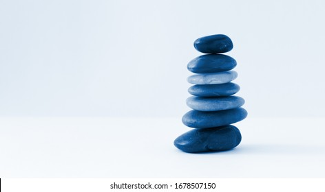 Balance, peace of mind, stones forming a pyramid on a white surface, minimalism, toned classic blue, 2020