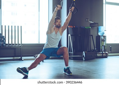 Balance and power. Full-length of young man in sportswear exercising at gym