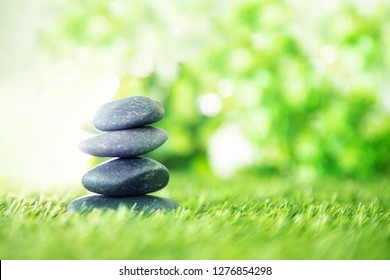 balance  with pyramid of stone on fresh nature green grass  , spa meditation or well-being with zen concept