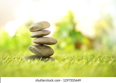balance  with a pyramid of stone on fresh nature green grass  , spa meditation or well-being with zen concept