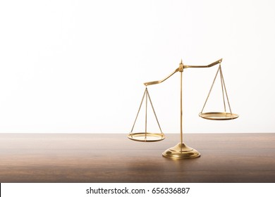 Balance scales on table with white wall background. Symbol of justice