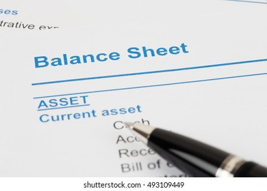 Balance Sheet in financial report book and pen, document is mock-up