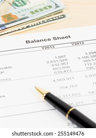 Balance sheet financial report with pen, and banknote; document is mock-up