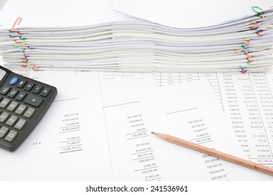 Balance sheet with pencil and calculator on finance account with pile of paperwork as background. Stack of paperwork is high as work hard. Business and finance concept rich and successful photography.