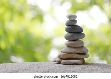 Balance stones are arranged in a pyramid shape,Stone Stacked on green nature background.
