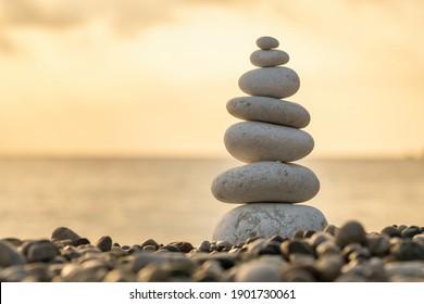 Balance stones close-up on the beach at sunrise