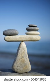 Balance of stones on a blue sky background with a copy space. To weight pros and cons.