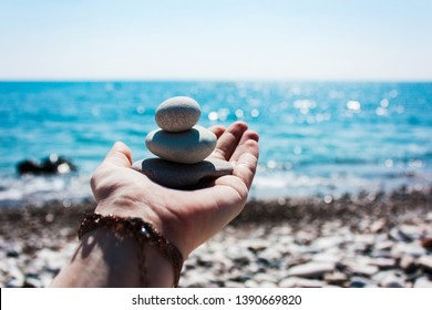Balance of stones on the hand against the background of the sea. The concept of peace of mind, harmony, spirituality