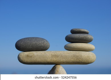 Balance of stones. To weight pros and cons. Balancing stones on the top of boulder. Close up. Balance of stones on a blue sky background with a copy space. Scales. Stones balance.