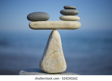 Balance of stones. To weight pros and cons. Balancing stones on the top of boulder. Close up. Balance of stones on a blue sky background with a copy space. Scales. Stones balance, sustainability.