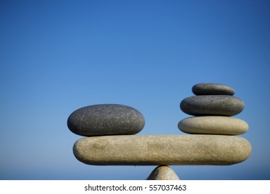 Balance of stones. To weight pros and cons. Balancing stones on a blue sky background with a copy space. Scales. Close up....