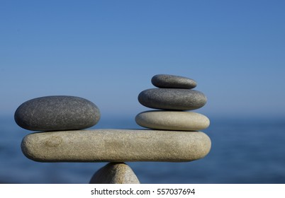Balance of stones. To weight pros and cons. Balancing stones on a blue sky and sea background with a copy space. Scales. Close up.