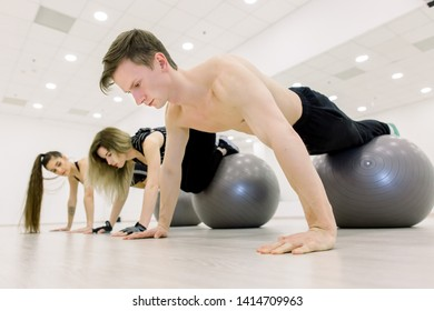 Balance, strength concept. Sporty man and two women do handstand with legs on fit ball. People in sportswear training on fitball in gym. Sport, fitness training.