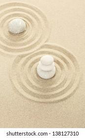 Balance of three zen stones in sand