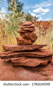 Balance and wellness concept. Close-up of a stack of rough red rocks with desert plants in the background.