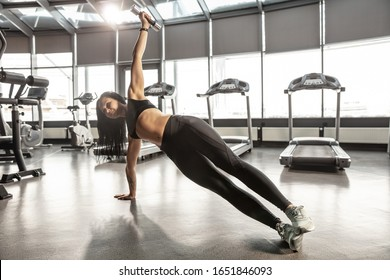Balance. Young muscular caucasian woman practicing in gym with weights. Athletic female model doing strenght exercises, training her upper body, hands. Wellness, healthy lifestyle, bodybuilding.