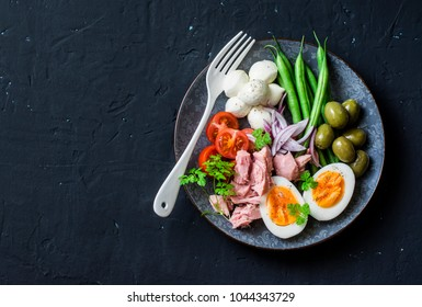 Balanced breakfast or snack - plate of canned tuna, green beans, mozzarella cheese, tomatoes, boiled egg, olives on a dark background, top view