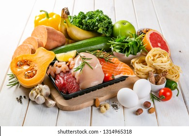 Balanced diet concept - fresh meat, fish, pasta, fruits and vegetables, nuts, seeds copy space