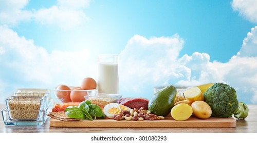 balanced diet, cooking, culinary and food concept - close up of vegetables, fruits and meat on wooden table over blue sky and clouds background