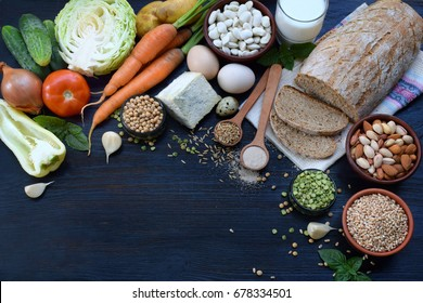 Balanced diet, cooking, dieting, culinary and food concept. Different foodstuffs - whole grain bread, cereal, vegetable, legumes, diary products, egg, nut, yeast. Healthy eating. Top view. Flat lay.