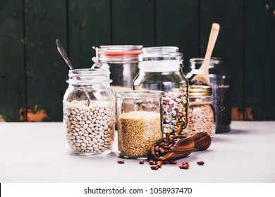 Balanced diet, cooking, vegetarian, raw and clean eating concept - Glass jars with various legumes and grains-beans, rice, lentils, bulgur and oat grains on concrete background